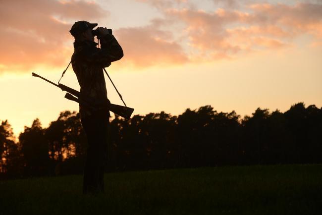 Jäger mit Fernglas bei Abenddämmerung