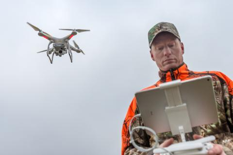 Jäger mit Drohne im Flug