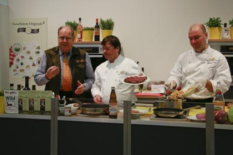 DJV-Präsident Hartwig Fischer unterstützt eine live Wildbret-Kochshow an einem benachbarten Stand
