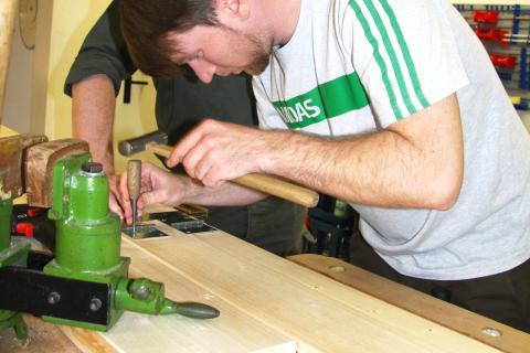 DJV-Volontär Sebastian Kapuhs probiert sich an der Holzschnitzbank.   (Quelle: djv)