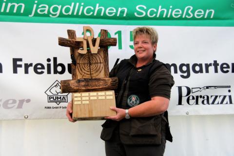 Siegerin mit neu gespendetem Wanderpokal. Die Siegerin schoss das höchste Ergebnis einer Damen bei einer Deutschen Meisterschaft. Der Pokal wurde aus einem Stück Holz mit der Motorsäge geschnitzt. (Quelle: Hunger/DJV)