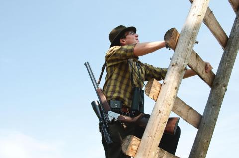 Jäger klettert auf den Hochsitz
