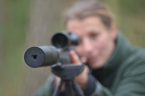 Eine Jägerin schießt mit einer Jagdwaffe mit Schalldämpfer