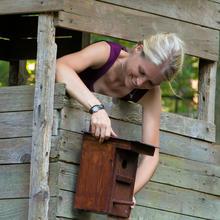 Jägerin bringt Nistkasten für Höhlenbrüter an Hochsitz an