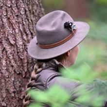 Frau mit Hut sitzt mit dem Rücken angelehnt an einem Baum.